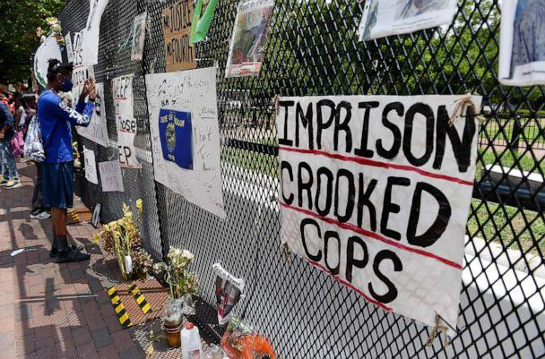 PHOTO: Signs hang on the fence surrounding Lafayette Park at Black Lives Matter Plaza, in Washington on July 25, 2020. (Olivier Douliery/AFP via Getty Images)