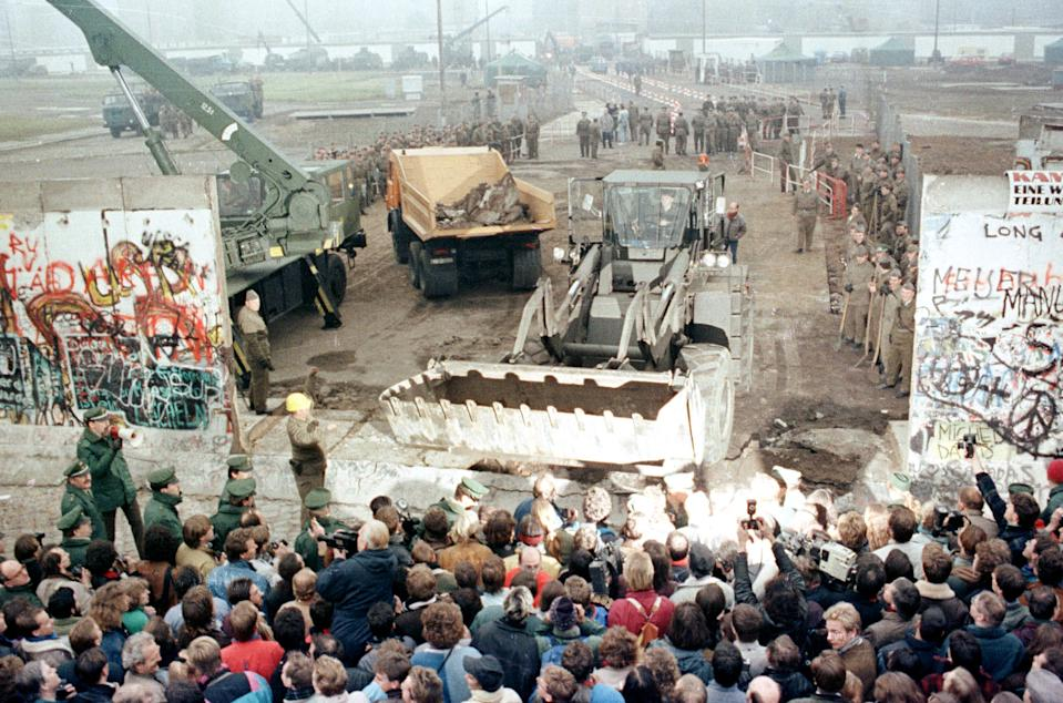 An East German bulldozer and crane knock down the Berlin Wall at Potsdamer Platz to make way for a new border crossing in the dvided city in this Nov. 12, 1989. (Photo: Wolfgang Rattay/Reuters)