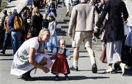 Anja List and her one-year old daughter Paulina wear traditional Bavarian Dirndls while visiting Munich's 180th Oktoberfest October 3, 2013. REUTERS/Michaela Rehle