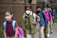 FILE - In this April 29, 2021, file photo, students line up to enter Christa McAuliffe School in Jersey City, N.J. Children are having their noses swabbed or saliva sampled at school to test for the coronavirus. As more children return to school buildings this spring, widely varying approaches have emerged on how and whether to test students and staff members for the virus. (AP Photo/Seth Wenig, File)
