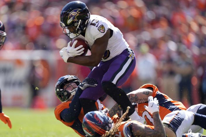 Baltimore Ravens wide receiver Devin Duvernay (13) it tackled against the Denver Broncos during the first half of an NFL football game, Sunday, Oct. 3, 2021, in Denver. (AP Photo/David Zalubowski)
