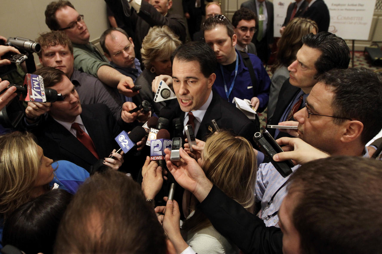 FILE - In this April 17, 2012 file photo, Wisconsin Gov. Scott Walker is surrounded by the news media after speaking to the Illinois Chamber of Commerce in Springfield, Ill. Ever since his fight to pass an anti-union bill last year, Walker has kept up a jet-setting schedule that's more akin to a candidate running for president than governor. More than a year after the standoff over union rights that rocked Wisconsin and the nation for weeks, the Republican Governor will face Milwaukee's Democratic Mayor Tom Barrett in Tuesday's recall election. (AP Photo/Seth Perlman, File)