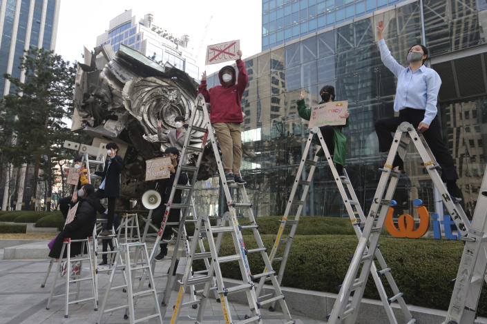 South Korean peace activists on the ladders stage a rally supporting Myanmar's democracy, outside the POSCO office in Seoul, South Korea on Feb. 22, 2021. POSCO Coated & Color Steel said Friday, April 16, 2021, it's ending a joint venture with a military-controlled firm in Myanmar following criticism that its business has benefited military leaders who have violently suppressed pro-democracy protests in the country. (AP Photo/Ahn Young-joon)