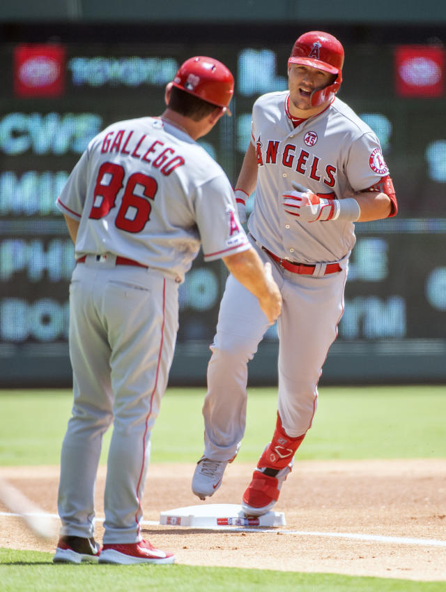 Los Angeles Angels' Mike Trout is congratulated by Los Angeles Angels third base coach Mike Gallego (86) after hitting a two run home run off of Texas Rangers starting pitcher Joe Palumbo that scored David Fletcher during the first inning of the first baseball game of a doubleheader Tuesday, Aug. 20, 2019, in Arlington, Texas. (AP Photo/Jeffrey McWhorter)