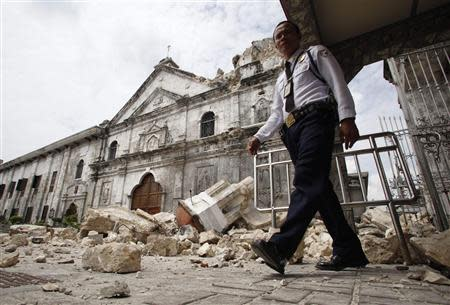 A security guard walks past the bell tower church of historic Basilica Minore of Sto Nino that fell down after an earthquake hit Cebu city