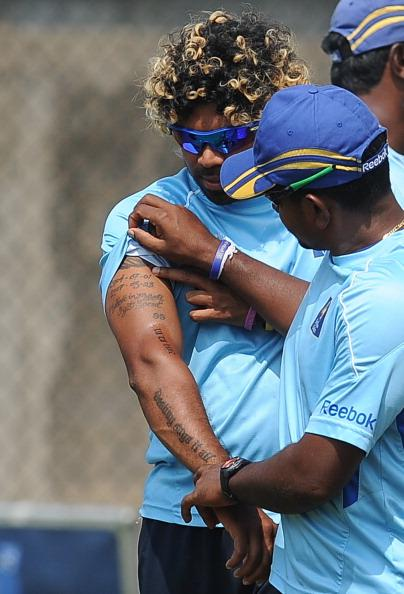 Sri Lankan spinner Rangana Herath (R) looks at tattoos on the arm of his teammate Lasith Malinga during a training session at the R. Premadasa Cricket Stadium in Colombo on March 28, 2011.  Sri Lanka face New Zealand in their Cricket World Cup semi-final match to be played in Colombo on March 29, 2011.  AFP PHOTO / Lakruwan WANNIARACHCHI (Photo credit should read LAKRUWAN WANNIARACHCHI/AFP/Getty Images)