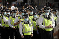 """Police officers wearing face masks stand next to a """"Resist and Act for Freedom"""" protest against a mandatory coronavirus vaccine, wearing masks, social distancing and a second lockdown, in Trafalgar Square, London, Saturday, Sept. 19, 2020. (AP Photo/Matt Dunham)"""