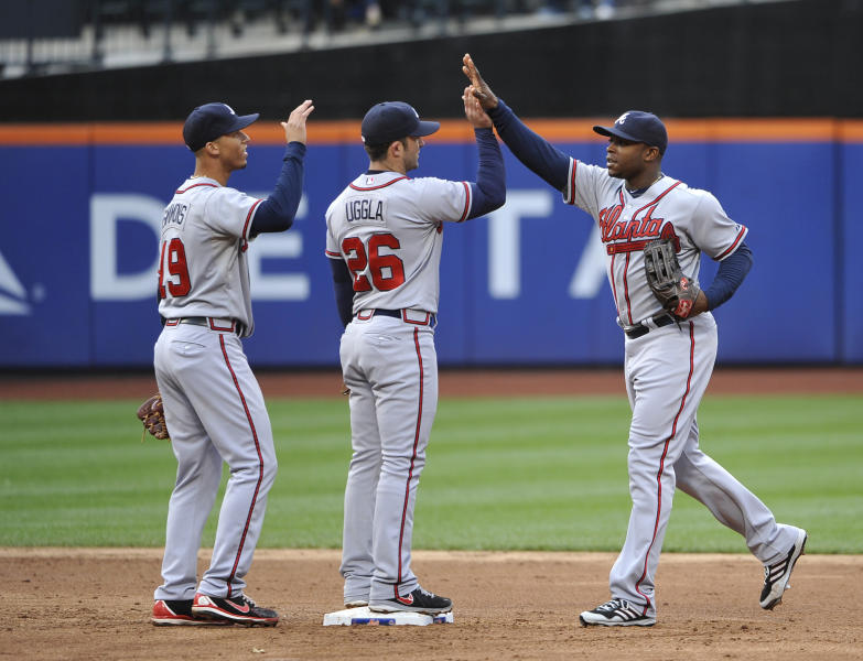 Atlanta Braves' Andrelton Simmons (19), Dan Uggla (26) and Justin Upton (8) celebrate their 7-5 win over the New York Mets in a baseball game that was suspended from Friday night due to rain at Citi Field, Saturday, May 25, 2013, in New York. (AP Photo/Kathy Kmonicek)