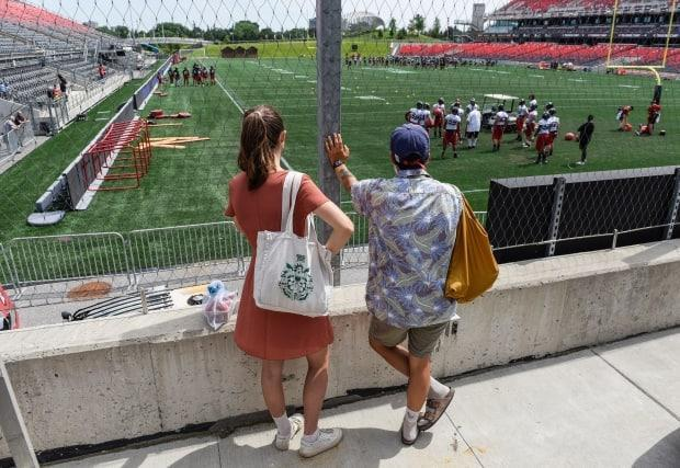 People watch the Ottawa Redblacks training camp from outside Lansdowne Park's TD Place in Ottawa on Monday. Their first home game of the pandemic-shortened season is scheduled for Aug. 28. (Justin Tang/The Canadian Press - image credit)