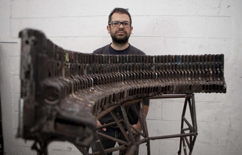 """**CORRECTS SPELLING OF BASS GUITAR** Mexican sculptor Pedro Reyes poses behind an instrument that mimics the sound of a basS guitar, made from seized guns, at his workshop in Mexico City, Tuesday, Feb. 13, 2013. The guns that have caused so many deaths in northern Mexico are transformed into musical instruments by Reyes. """"It's important to consider that many lives were taken with these weapons, as if a sort of exorcism was taking place,"""" says Reyes in a description ofhis project titled, """"Disarm."""" The Mexican artist said he was able to choose his instruments from about 6,700 guns that were turned in or seized by the army and police in Ciudad Juarez, a city of about 1.3 million people that averaged about 10 killings a day at the height of the violence. (AP Photo/Eduardo Verdugo)"""