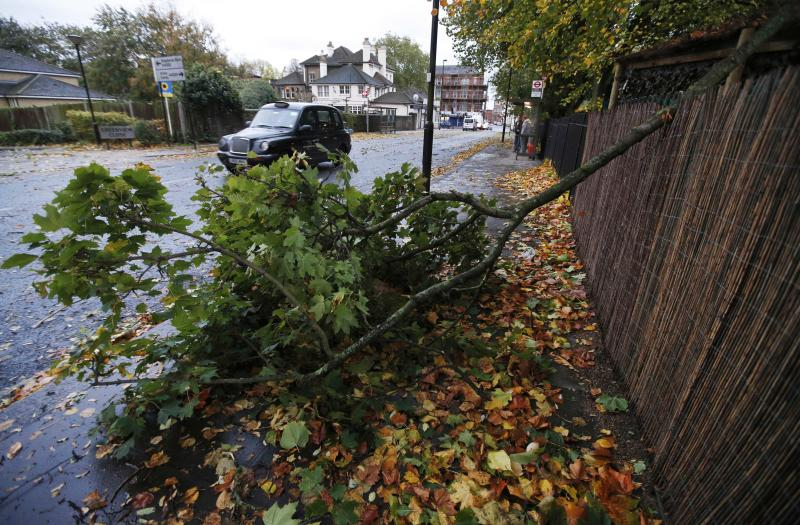 A fallen tree branch partially blocks a pavement in London, Monday, Oct. 28, 2013. A major storm with hurricane-force winds is lashing southern Britain, causing flooding and travel delays including the cancellation of roughly 130 flights at London's Heathrow Airport. Some rail lines shut down Monday morning, and some roads were closed due to fallen trees and power lines. Air travelers and commuters were advised to check conditions before starting any journeys. Widespread delays were expected as major London train lines delayed their opening because of the winds and tree hazards.(AP Photo/Lefteris Pitarakis)