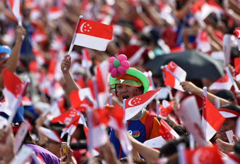 Spectators wave Singaporean national flags during their country's 52nd National Day parade and celebration in Singapore on 9 August, 2017. (AFP via Getty Images file photo)