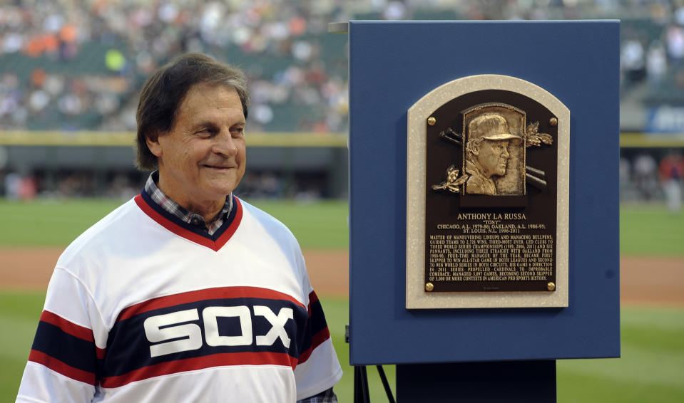 FILE - In this Aug. 30, 2014, file photo, former Chicago White Sox manager Tony La Russa stands with his Baseball Hall of Fame plaque before the second baseball game of a doubleheader against the Detroit Tigers in Chicago. La Russa, the Hall of Famer who won a World Series championship with the Oakland Athletics and two more with the St. Louis Cardinals, is returning to manage the Chicago White Sox 34 years after they fired him, the team announced Thursday, Oct. 29, 2020. (AP Photo/Matt Marton, File)