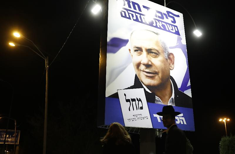 A woman and an ultra-Orthodox Jewish man walk past a billboard displaying Israeli Prime Minister Benjamin Netanyahu in Jerusalem (AFP Photo/Ahmad GHARABLI)