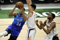 Milwaukee Bucks' Giannis Antetokounmpo, left, drives to the basket against Phoenix Suns' Devin Booker, center, and Mikal Bridges, right, during the first half of an NBA basketball game Monday, April 19, 2021, in Milwaukee. (AP Photo/Aaron Gash)