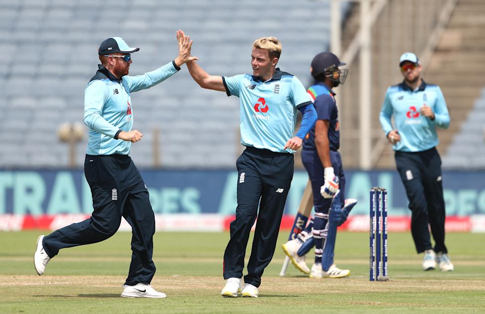 PUNE, INDIA - MARCH 26: England bowler Sam Curran (r) is congratulated by Jonathan Bairstow after taking the wicket of India batsman Rohit Sharma during the 2nd One Day International between India and England at MCA Stadium on March 26, 2021 in Pune, India. (Photo by Surjeet Yadav/Getty Images)