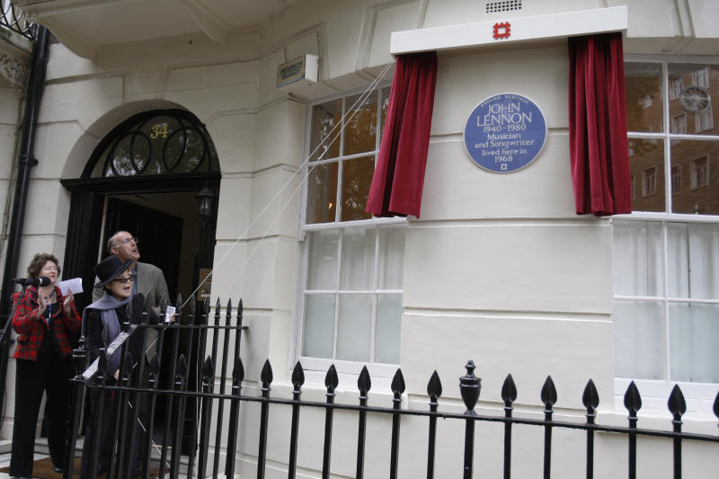 Japanese artist and musician Yoko Ono, left center, unveils a Blue Plaque honouring British musician John Lennon during an unveiling ceremony at 34 Montagu Square in London, Saturday, Oct. 23, 2010. John Lennon is commemorated with an English Heritage blue plaque in celebration of his life and contribution to music at the flat where he shared his first home with Yoko Ono and where the famous nude photograph of John and Yoko was taken for the 'Two Virgins' album cover. (AP Photo/Sang Tan)