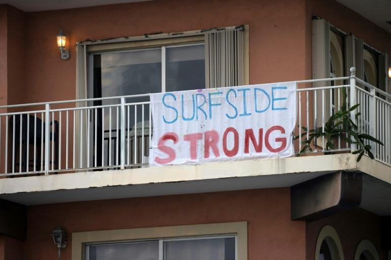 """A """"Surfside Strong"""" sign hangs on a balcony as search and rescue operations continue at the site of the partially collapsed 12-story Champlain Towers South condo building"""