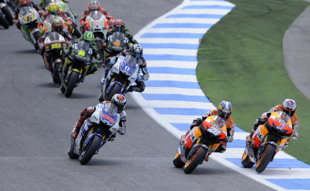 Repsol Honda team's Australian Casey Stoner (R), Spanish Dani Pedrosa (C) and Yamaha Factory Racing rider Spanish Jorge Lorenzo (L) lead the pack during the first lap of the Moto GP race of the Portuguese Grand Prix in Estoril, outskirts of Lisbon, on May 6, 2012. Stoner won the race ahead of Lorenzo and Dani Pedrosa. AFP PHOTO / MIGUEL RIOPAMIGUEL RIOPA/AFP/GettyImages