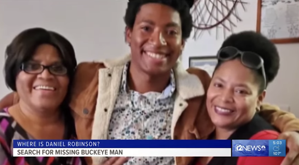 Daniel smiling in photo with two women