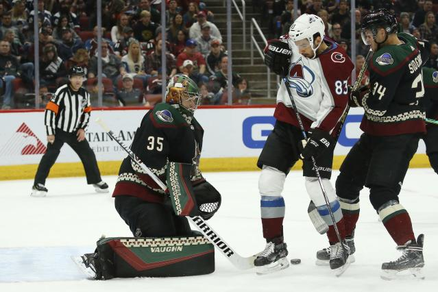 Arizona Coyotes goaltender Darcy Kuemper (35) makes a save as Colorado Avalanche left wing Matt Nieto (83) and Coyotes center Carl Soderberg (34) battle for position during the first period of an NHL hockey game Saturday, Nov. 2, 2019, in Glendale, Ariz. (AP Photo/Ross D. Franklin)