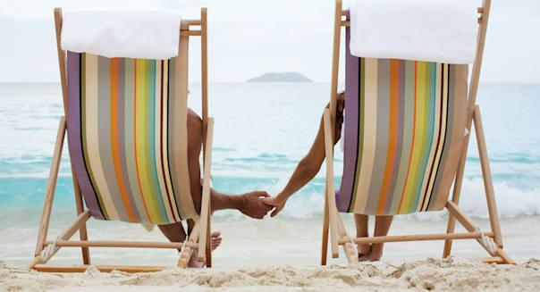 Couple on lounge chairs, holding hands (rear view), St. John, US Virgin Islands, USA