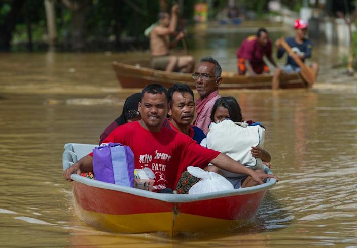 A family ride in a boat through floodwater in Pengkalan Chepa, near Kota Bharu on December 26, 2014 (AFP Photo/)