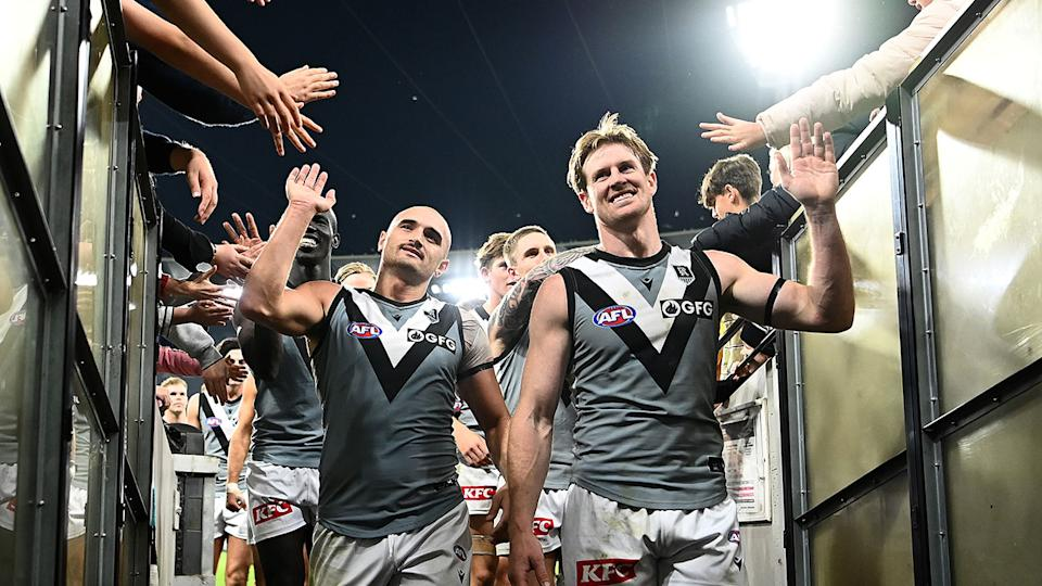 Pictured here, Port Adelaide players celebrate after their victory over Collingwood.