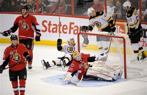 Boston Bruins' David Krejci, second from right, celebrates his game-winning goal with teammate Milan Lucic, center, and Benoit Pouliot, right, as Ottawa Senators goalie Alex Auld gets up off the ice and Senators Erik Condra, left, and Matt Carkner skate away during the third period of an NHL hockey game in Ottawa, Ontario, on Saturday, Feb. 25, 2011. The Bruins defeated the Senators 5-3. (AP Photo/The Canadian Press, Sean Kilpatrick)