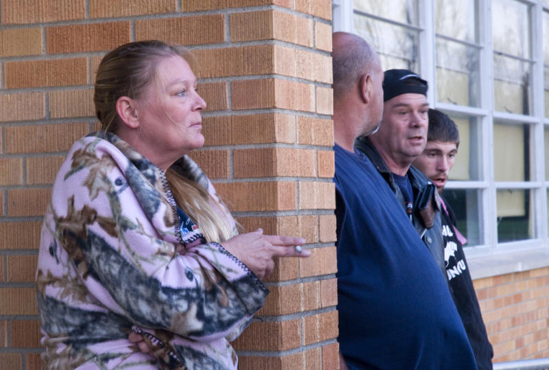 Lisa Johnson smokes outside with other residents of West Point, Ky., living within a mile-and-a-half radius of the site of a train derailment wait at a Red Cross shelter Wednesday, Oct. 31, 2012 at the Muldraugh Elementary School in Muldraugh, Ky., after being asked to evacuate. A Paducah & Louisville Railway train carrying hazardous chemicals derailed just after 6 a.m. EDT Monday and a leak of a potentially explosive material was contained, but authorities say three workers were severely burned in a fire that erupted while contractors were removing debris from the train today in southwest Louisville, Ky. (AP Photo/Brian Bohannon)