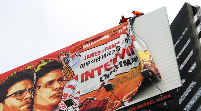 "Workers remove the poster for ""The Interview"" from a billboard in Hollywood, California, December 18, 2014 (AFP Photo/Veronique Dupont)"