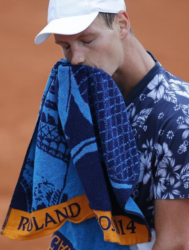 Tomas Berdych of the Czech Republic wipes his face as he plays Latvia's Ernests Gulbis during their quarterfinal match of the French Open tennis tournament at the Roland Garros stadium, in Paris, France, Tuesday, June 3, 2014. Gulbis won 6-3, 6-2, 6-4. (AP Photo/David Vincent)