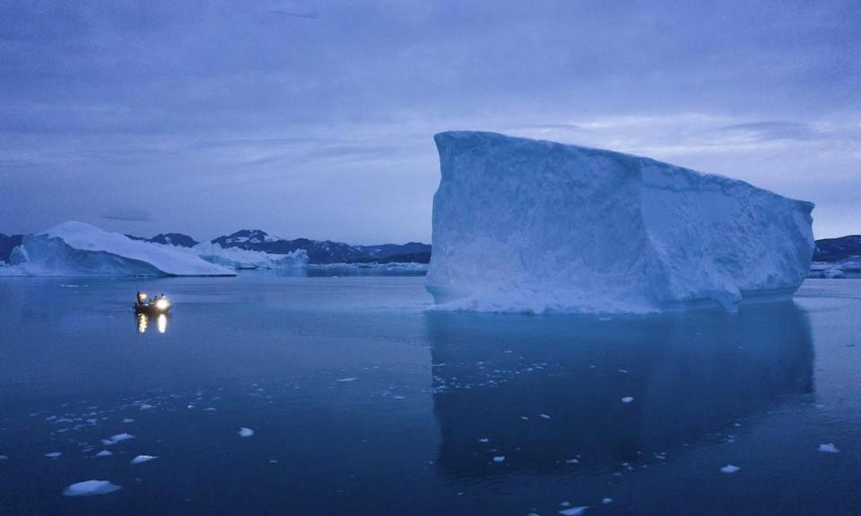 A boat navigates a large iceberg in eastern Greenland.