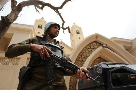 An armed policeman secures the Coptic church that was bombed on Sunday in Tanta