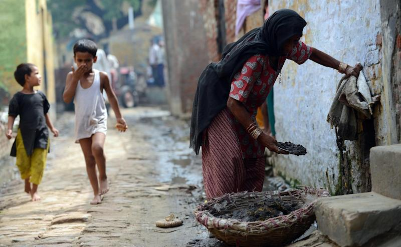 File photo taken on August 10, 2012 shows 60-year-old manual scavenger Kela collecting human waste while cleaning a toilet in Nekpur village, Muradnagar in Uttar Pradesh, some 40kms east of New Delhi