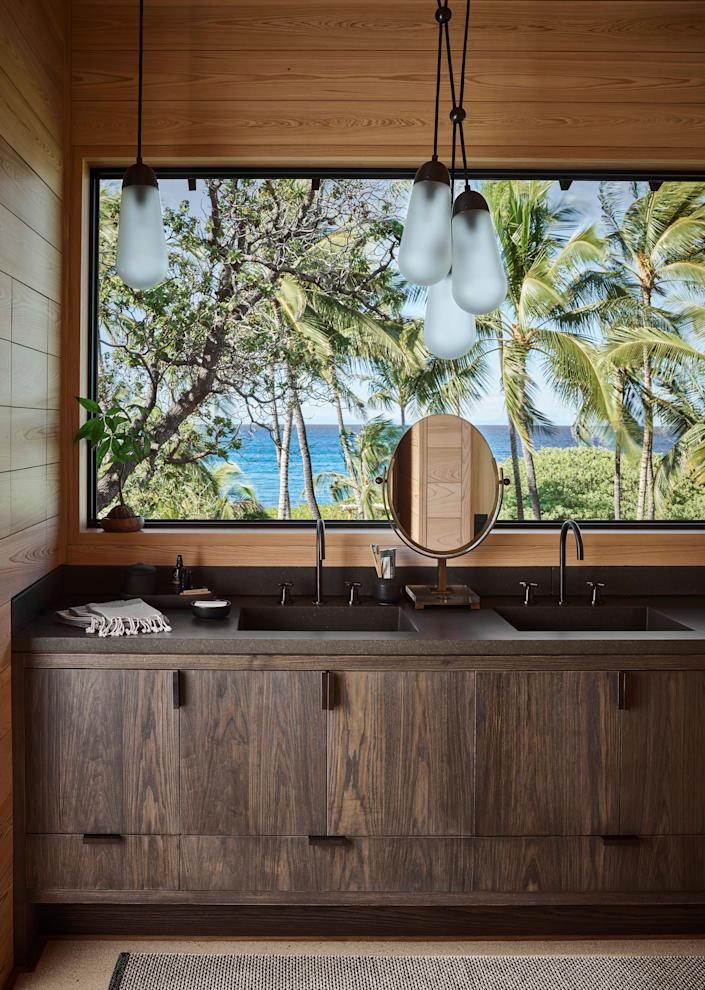 The bathroom of the primary bedroom features a postcard window that frames a quintessential Hawai'ian scene. The custom stained-ash vanity with cast-concrete sink is purposeful but modest, a grounding, earthy element to anchor the view of sea and sky. Larian pendants by Apparatus Studio, Charles Hollis Jones mirror.