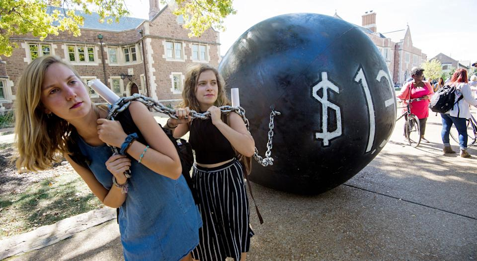 """Students pull a mock """"ball & chain"""" representing the $1.4 trilling outstanding student debt at Washington University in St. Louis, Missouri, where second presidential debate will be held between Republican nominee Donald Trump and his Democratic counterpart Hillary Clinton / AFP / PAUL J. RICHARDS        (Photo credit should read PAUL J. RICHARDS/AFP via Getty Images)"""