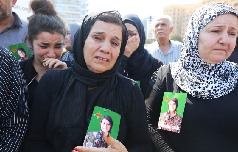 A Kurdish woman living in Lebanon, who has a picture of Hevrin Khalaf placed on her chest, reacts during a protest against Turkey's military action in northeastern Syria, in Beirut