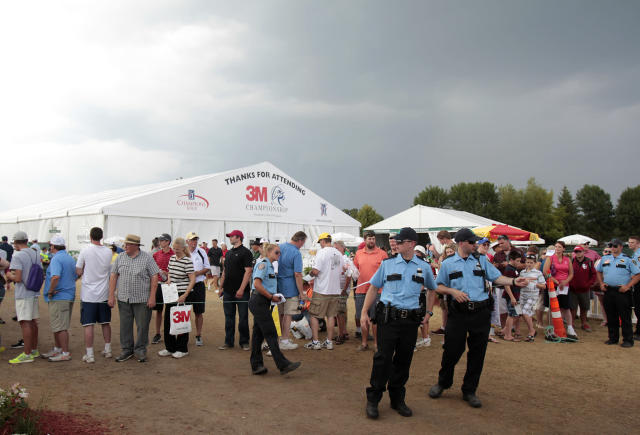 Security personnel manage the crowd after a weather delay was issued during the second round of the Champions Tour's 3M Championship golf tournament at TPC Twin Cities in Blaine, Minn., Saturday, Aug. 2, 2014. AP Photo/Paul Battaglia)