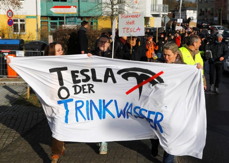 Demonstrators hold anti-Tesla posters during a protest against plans by U.S. electric vehicle pioneer Tesla to build its first European factory and design center near Berli
