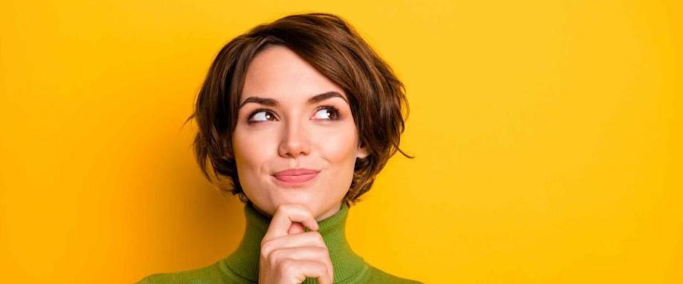 Closeup photo of lady in green turtleneck thinking