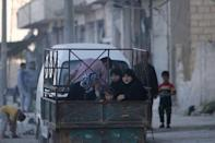 Reisidents ride on the back of a pick-up truck in Manbij, in Aleppo Governorate, Syria, August 9, 2016. REUTERS/Rodi Said
