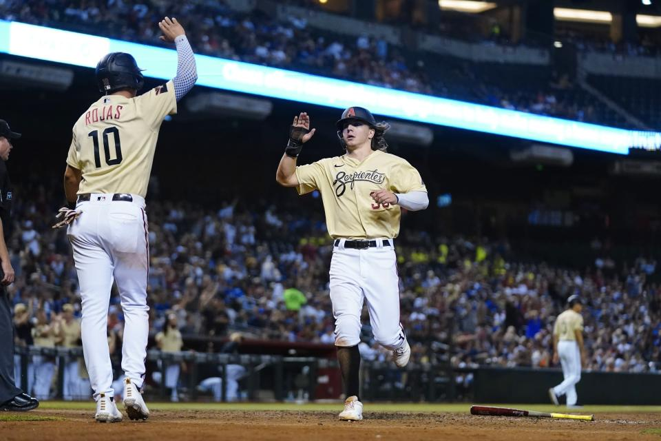 Arizona Diamondbacks' Josh Rojas (10) and Jake McCarthy, right, celebrate their runs against the Los Angeles Dodgers during the eighth inning of a baseball game Saturday, Sept. 25, 2021, in Phoenix. (AP Photo/Ross D. Franklin)