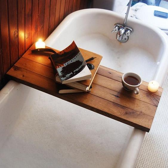 "Enlist a Tub Caddy  There are few things as relaxing—or spa-indulgent—as a nice, long soak in the tub. This handsome wood Tub Caddy from Peg & Awl makes the ""soak"" that much more enjoyable by providing a convenient place to set a book, a cup of tea, or a glass of wine. The caddy is made of reclaimed oak beams and finished with two coats of pure tung oil, making it water resistant and easy to clean. Etsy, $20 (Photo:  Peg & Awl)"