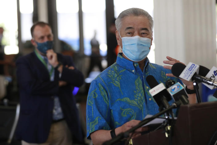FILE - In this Oct. 15, 2020 file photo, Hawaii Gov. David Ige speaks at a news conference as Lt. Gov. Josh Green, left, looks on at the Daniel K. Inouye International Airport in Honolulu. A pre-travel testing program that allows visitors who test negative for COVID-19 to come to Hawaii and avoid a mandatory quarantine went into effect on Oct. 15. The small, tight-knit community of about 72,000 people on the island of Kauai in Hawaii spent the first seven months of the pandemic mostly COVID-free. Then in October, when statewide travel restrictions eased, the pandemic came pouring in. (AP Photo/Marco Garcia, File)