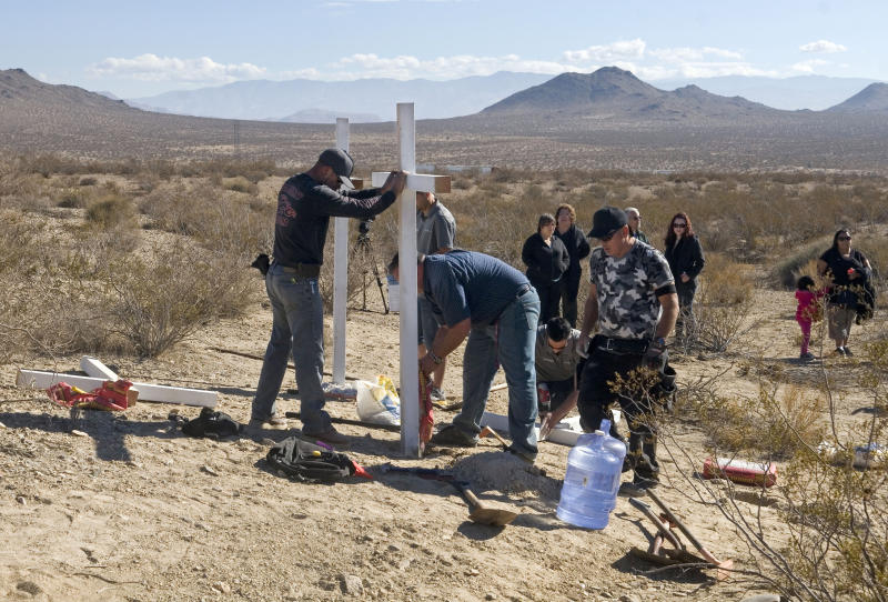 Photo showing residents of Victorville place crosses near the graves where the McStay family's remains were found.