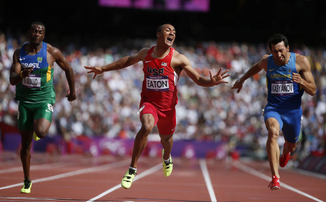 Ashton Eaton of the U.S. wins in the men's decathlon 100m heat next to Brazil's Luiz Alberto de Araujo (L) and Ukraine's Oleksiy Kasyanov (R) during the London 2012 Olympic Games at the Olympic Stadium August 8, 2012. REUTERS/Lucy Nicholson (BRITAIN - Tags: OLYMPICS SPORT ATHLETICS TPX IMAGES OF THE DAY)