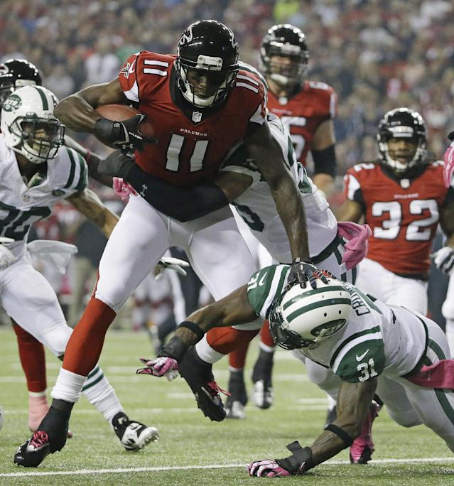 Atlanta Falcons wide receiver Julio Jones (11) is hit by New York Jets free safety Antonio Allen (39) and New York Jets cornerback Antonio Cromartie (31) during the first half of an NFL football game, Monday, Oct. 7, 2013, in Atlanta. (AP Photo/David Goldman)