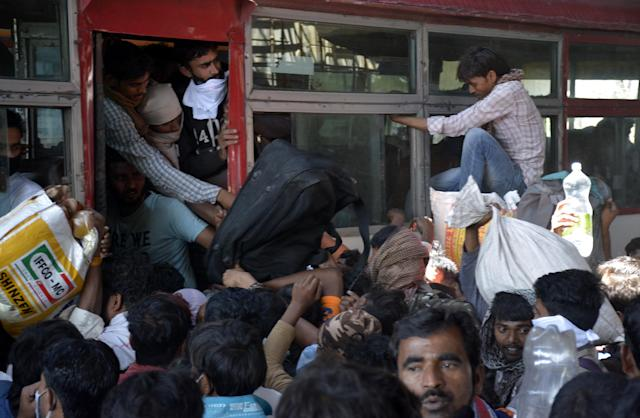 GHAZIABAD, INDIA - MARCH 28: Migrant workers try to board an overcrowded bus bound to their native state on Day 4 of the 21 day nationwide lockdown -- to check the spread of coronavirus, at Lal Kuan bus stand, on March 28, 2020 in Ghaziabad, India. (Photo by Sakib Ali/Hindustan Times via Getty Images)