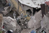 First responders conduct a rescue for survivors amid a three-story pile of rocks in Tlalnepantla, on the outskirts of Mexico City, when a mountain gave way on Friday, Sept. 10, 2021, plunging rocks the size of small homes onto a densely populated neighborhood. (AP Photo/Eduardo Verdugo)